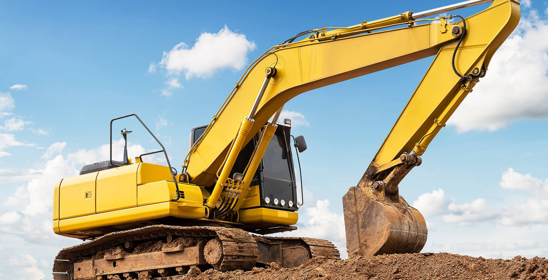 Excavator backhoe on the ground at construction site in blue sky background